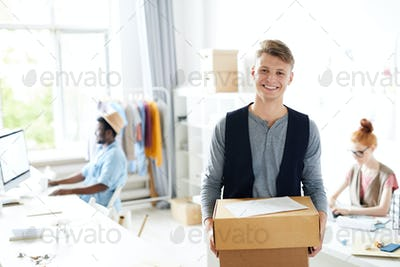 Young designer standing with parcel