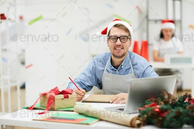 Happy creative designer in Santa hat