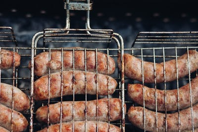 Sausages on grill at bbq party.Close-up of delicious chicken or pork sausages on BBQ. Unrecognizable