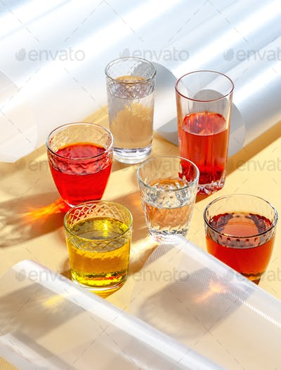Glass cups with colorful cold drinks on a yellow background with