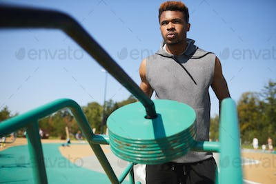Black man breathing out while training with workout equipment
