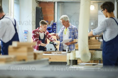 Senior carpenter foreman giving advice to inexperienced employee