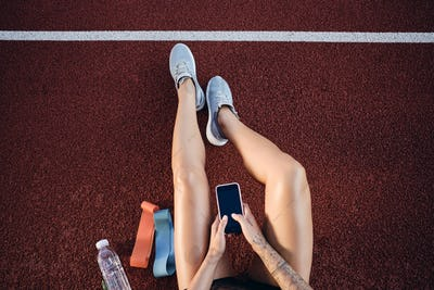 Top view of sporty girl with cellphone resting after workout on stadium