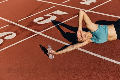 Tired athlete girl in sportswear lying on runner track dreamily covering eyes with hand from sun