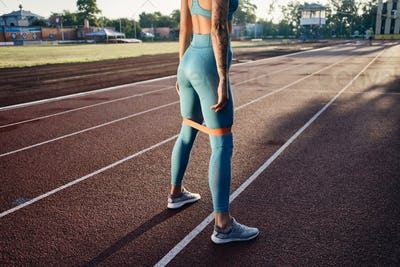 Close up sporty girl in stylish sportswear training with rubber band on city stadium