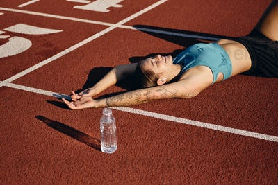 Glad athlete girl in sportswear happily lying on runner track with bottle after workout on stadium