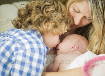 Beautiful Young Mother Holds Precious Newborn Baby Girl as Brother Looks On.