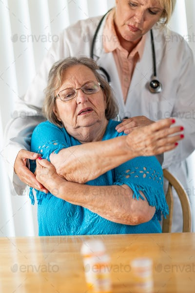 Female Doctor Helping Senior Adult Woman With Arm Exercises.