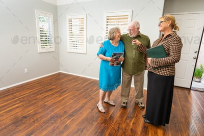 Female Real Estate Agent Handing New House Keys to Senior Adult Couple In New Home.