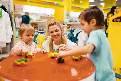 Mother with little children playing in kids store