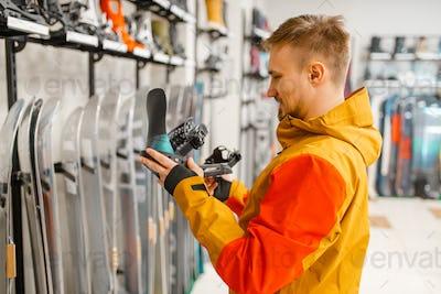 Man choosing ski boot fastening in sports shop