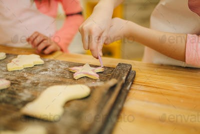 Little girls cooks cover cookies with sweet layer