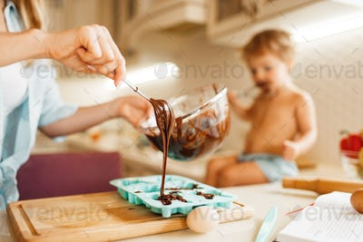 Mother and kid cooking and tastes melted chocolate