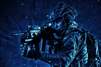Soldier aiming service rifle under rain at night