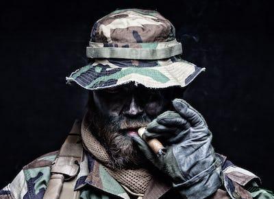 Commando soldier in boonie hat smoking cigar