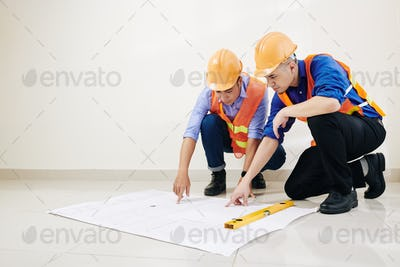 Engineers checking blueprint details