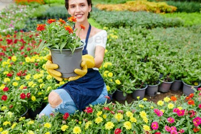 Happy woman showing plant she grown