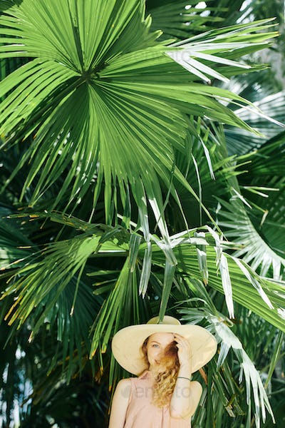 Cheerful woman standing under palm tree