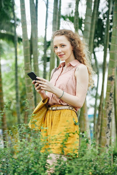 Pretty texting woman in park