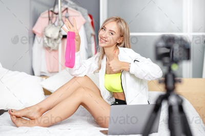 Pretty young girl blogger dressed in fashionable clothes is being filmed for advertising sitting on