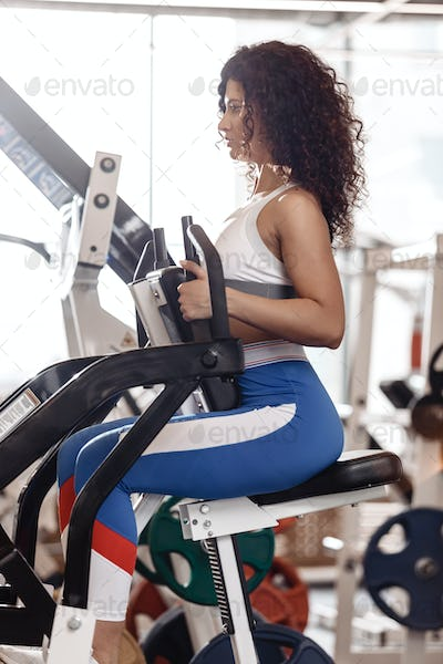 Young curly good fit girl dressed in sports clothes is doing exercise on the sports equipment in the