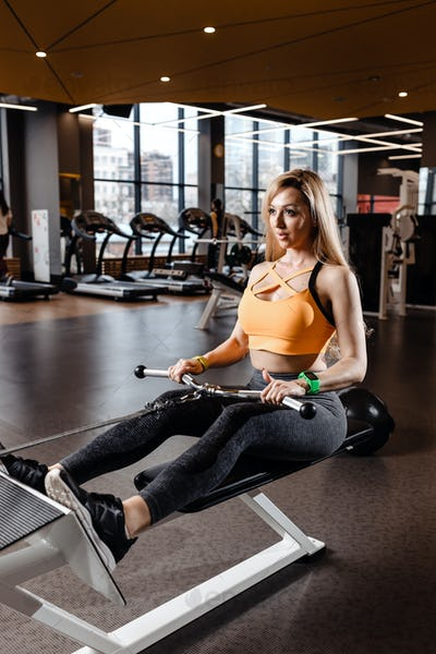The beautiful athletic girl with long blond hair dressed in a sportswear is doing sport exercises