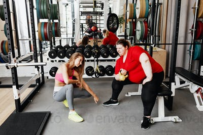 Fat girl in the sportswear works out with the weight in the gym under the supervision of a strict
