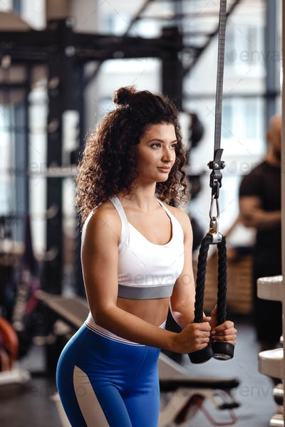 Athletic curly girl has a TRX workout in the modern gym full of sun light