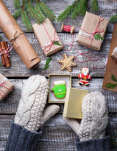 Woman  in mittens packing Christmas gift boxes
