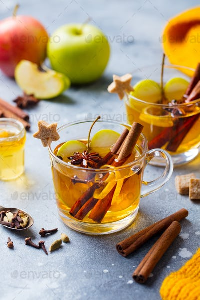 Apple Mulled Cider with Spices in Glass Cup. Grey Background.