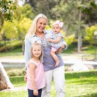 Happy Young Caucasian Mommy and Daughters Portrait In The Park.