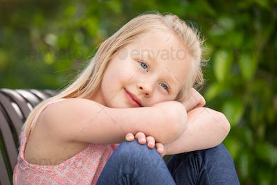 Pretty Young Caucasian Girl Portrait Sitting On The Bench At The Park.