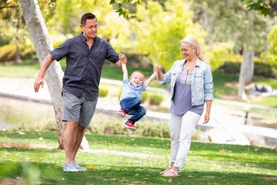 Young Mother and Father Swingging Their Son At The Park.
