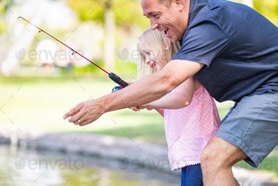 Young Caucasian Father and Daughter Having Fun Fishing At The Lake.