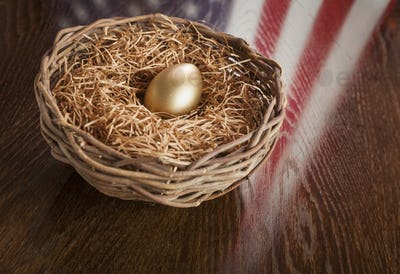 Golden Egg in Nest with American Flag Reflection on Wooden Table.