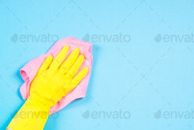 Hand in yellow gloves and microfiber rag cleaning blue background