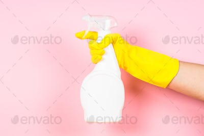 Hand in yellow gloves hold cleaning agent bottle on pink background