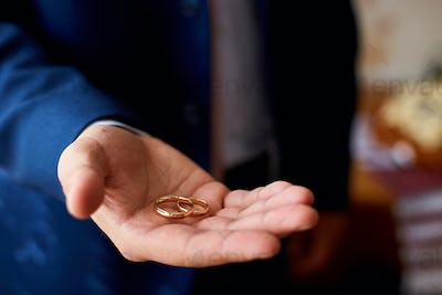 Groom holding wedding rings on the palm