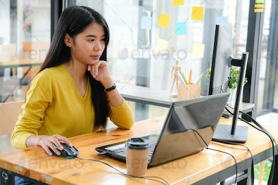 Asian female programmers in yellow shirts are using laptop and PC.
