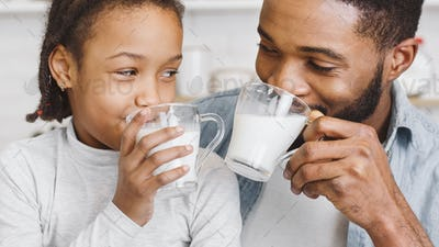 Black little girl and her father drinking fresh milk