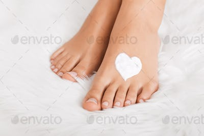 Perfect female feet with heart shaped cream spot, close up