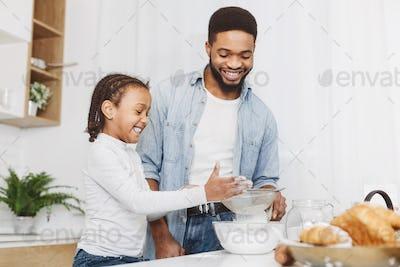 Black little girl sieving flour for pastry dough