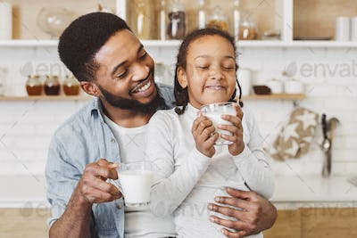 African father encouraging daughter to drink milk