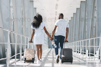 African american man and woman going on departure with luggage