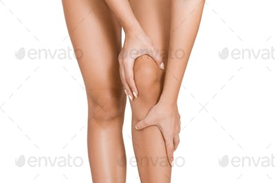 Young woman touching her inflamed knee with acute pain