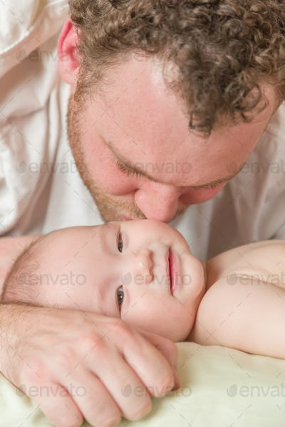 Mixed Race Chinese and Caucasian Baby Boy Laying In Bed with His Father.