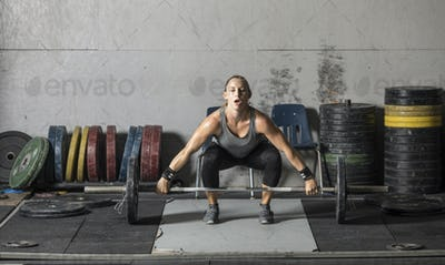 Strong woman preparing to lift heavy barbell in gym.