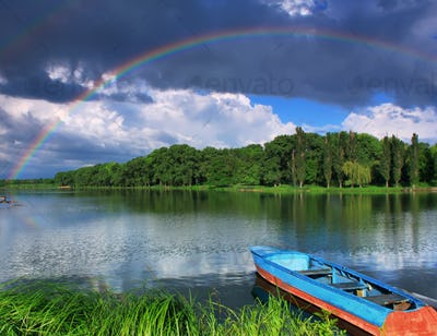 Rainbow over the lake with a boat