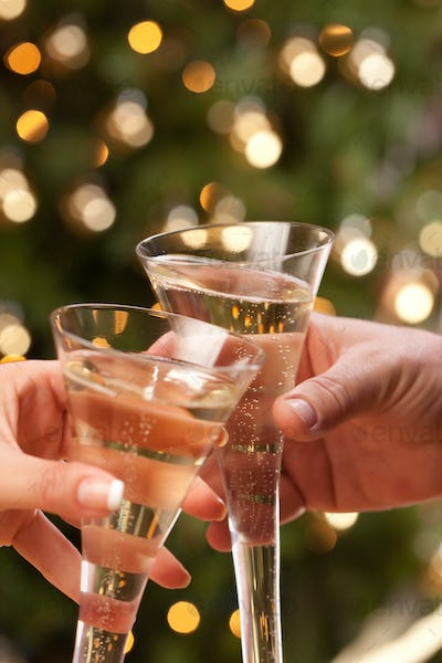 Man and Woman Toasting Champagne in Front of Decor and Lights.