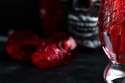 Halloween bloody glass with a human skeleton face as cup on black background